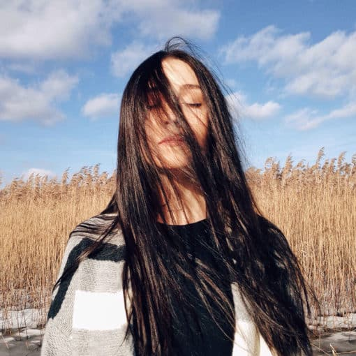 Girl with long brunette hair that is really shiny. Standing a cane field.