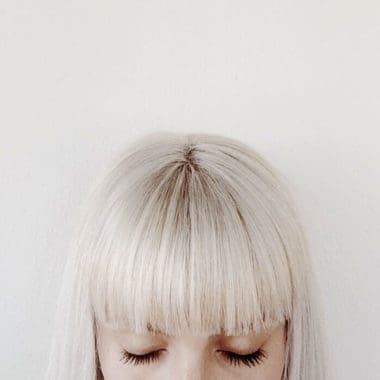 Picture of half a girls head with a bob and big blunt fringes with white blonde hair.