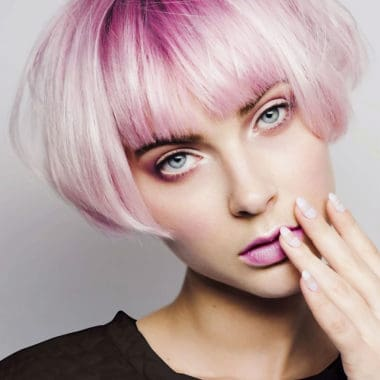 Vibrant pink pixie hair cut and model with pink lipstick and long manicured french nails